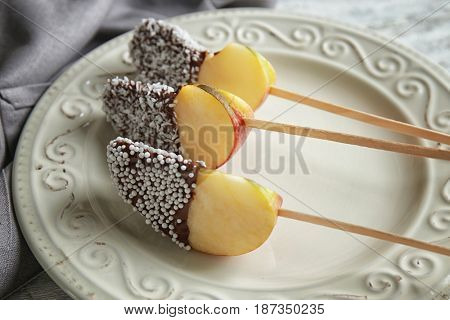 Plate with candied apple wedges on sticks
