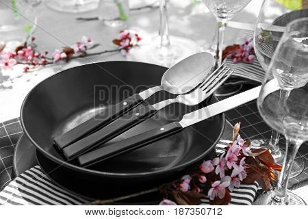 Plates with cutlery on served festive table