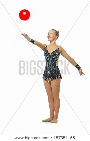 beautiful blond teen age gymnast girl making exercises with red ball. Studio shot isolated on white background. Copy space.