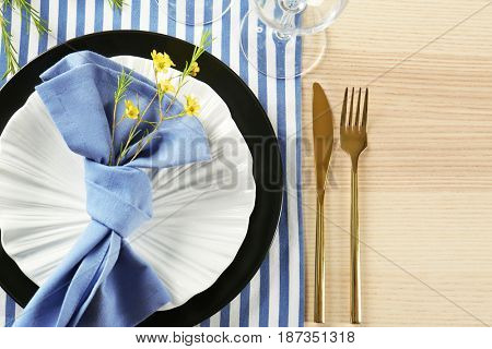 Table setting with lilac color napkin and floral decor on wooden surface