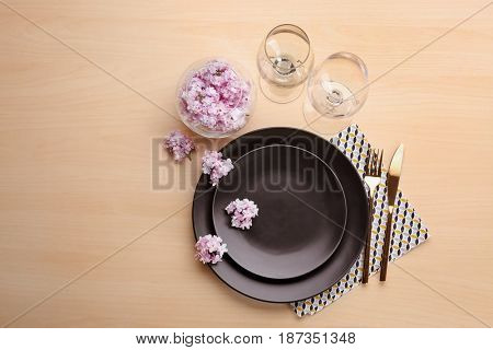 Beautiful festive table setting with lilac flower decor on wooden surface