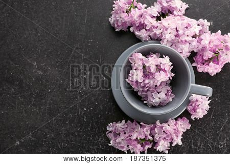 Cup with saucer and lilac floral decor on dark background