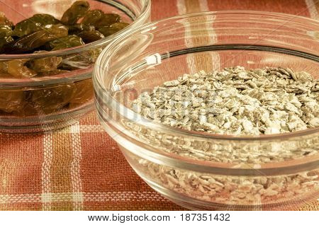 Oat flakes and raisins in a glass bowl on colorful dishcloth. Closeup shot. Healthy food concept. Toned.
