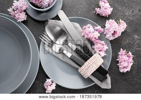 Beautiful festive table setting with lilac flower decor on dark background