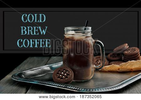 Glass jar of cold brewed coffee with cookie on black background