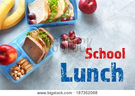 Concept of school lunch. Lunchboxes and food on gray background