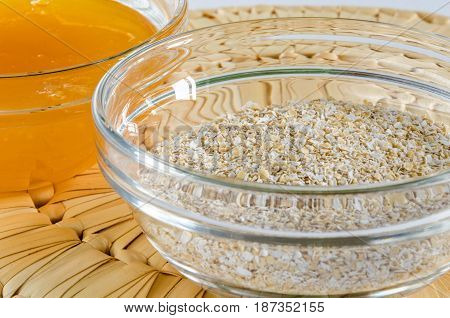 Oat bran and honey in a glass bowl on straw hot pad. Closeup shot. Healthy food concept.
