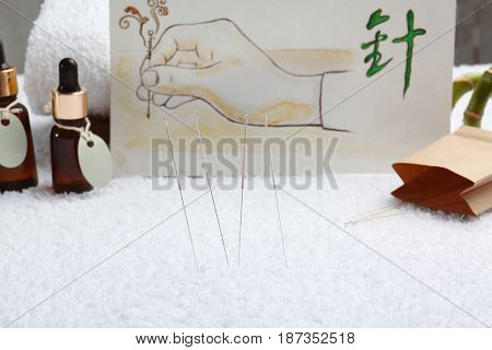 Acupuncture needles and blurred drawing on background
