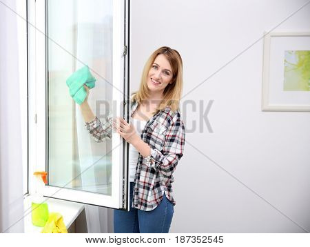 Young woman cleaning window at home