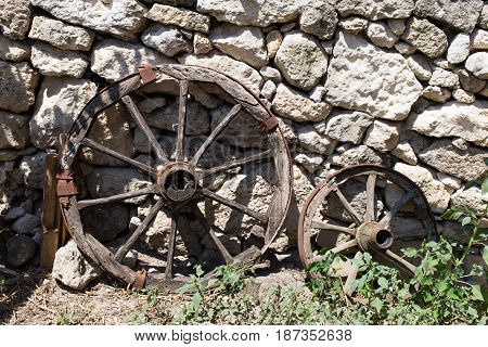 Old cart wooden wheels neat stone wall as a background.