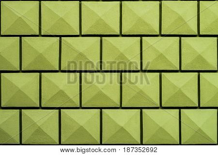 Atypical green wall facing green pyramid pattern background