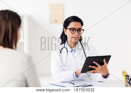 medicine, healthcare, technology and people concept - doctor with tablet pc computer and woman patient meeting at hospital