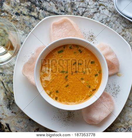 Creamy crab soup served with crab chips and glass of white wine on marble backround. Top view or flat lay.
