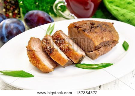 Duck breast with green onion in a white oval plate, fruits on a wooden plank background