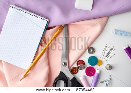 needlework and tailoring concept - scissors, sewing buttons, spools of thread, cloth and notepad with pencil