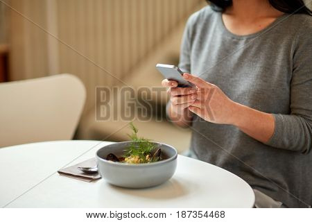 food, new nordic cuisine, technology, eating and people concept - woman sitting at cafe table with smartphone and bowl of soup
