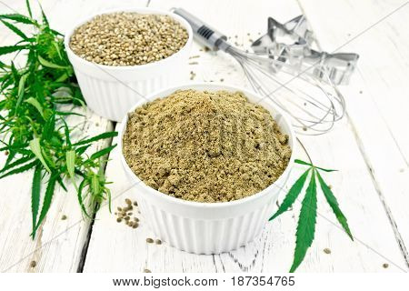 Flour and hemp grain in bowls, mixer and cookie cutters, cannabis leaves on the background of wooden boards