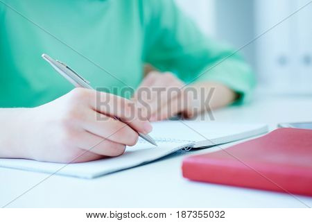 Female hands holding a silver pen closeup. Business woman making notes at office workplace. Business job offer financial success certified public accountant concept.