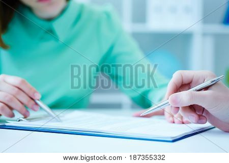 Young female employee of the staffing agency helps fill out the form to the male job seeker. Business office law and legal concept.