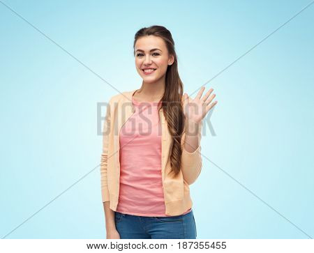 gesture and people concept - happy smiling young woman in cardigan waving hand over blue background