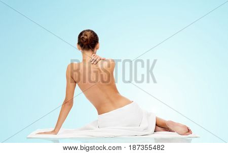 beauty, people and bodycare concept - beautiful young woman in white towel with bare top over blue background