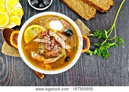 Soup saltwort with lemon, meat, pickles, tomato sauce olives in a bowl on a sacking, bread on a background of a wooden board from above
