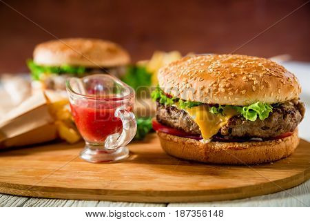 Classic hamburger with beef and tomato sauce on wooden plate. Tasty food concept