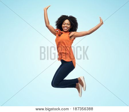 people, ethnicity and motion concept - happy african american young woman jumping over blue background