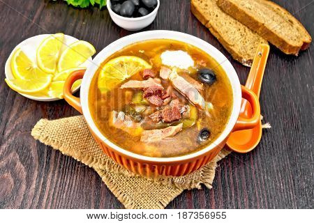 Soup saltwort with lemon, meat, pickles, tomato sauce olives in a bowl on a sacking, bread, parsley and spoon on a wooden board background