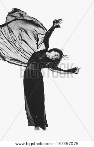 Beautiful modern dancer young woman in black flyings fabrics making dance moves. Isolated on white background. Copy space. Monochrome.