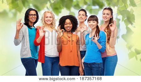diversity, race, ethnicity and people concept - international group of happy smiling different women showing ok hand sign over green natural background