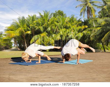 fitness, sport, yoga and people concept - couple making side crane pose on mat over natural background with palm trees