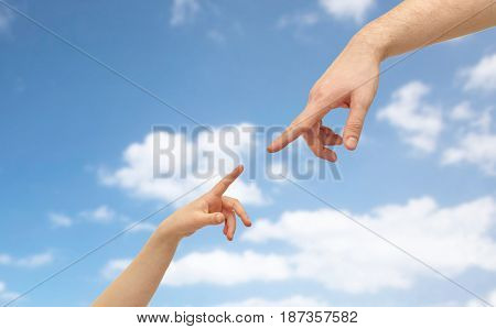family and people concept - father and child hands pointing fingers to each other over blue sky and clouds background