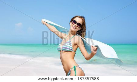 travel, people, summer holidays and vacation concept - beautiful woman in bikini and sunglasses with pareo over exotic tropical beach background