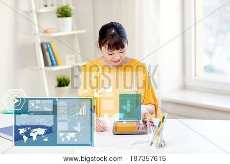 people, education, high school and technology concept - happy asian young woman student with tablet pc computer, book and notepad writing at home