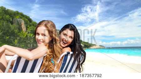 summer holidays, people, leisure, vacation and travel concept - happy women sunbathing on folding chairs over exotic tropical beach background
