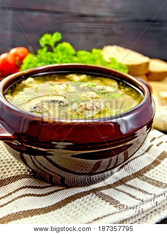 Soup with meatballs, noodles and champignon in a clay bowl on a towel, parsley, tomatoes, mushrooms and bread on dark background wooden plank