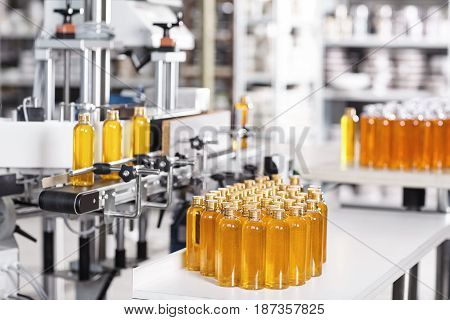 Cosmetics Factory. Bottling Line Filled With Yellow Shampoo. Automated Process On Factory. Line Of B