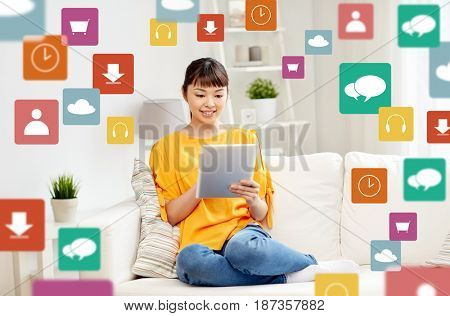 people, multimedia and technology concept - happy young asian woman sitting on sofa with tablet pc computer at home
