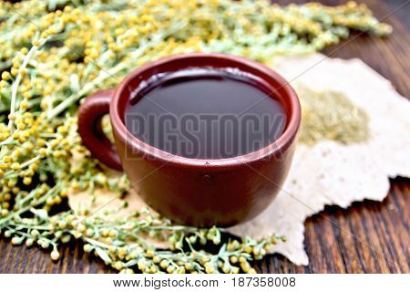 Herbal tea in a brown clay cup, twigs gray sagebrush, wormwood dried on a paper on the background of wooden boards