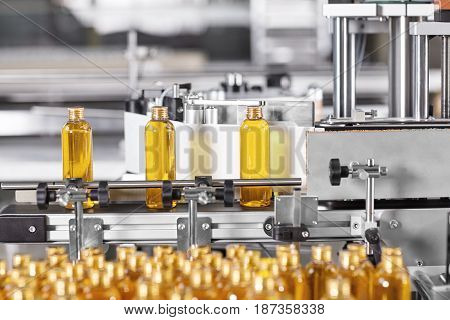 Factory Process Of Production New Cosmetics. Glass Bottles Standing On Conveyor Line Going To Be Twi
