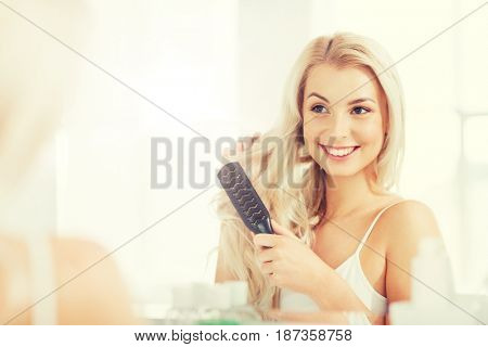 beauty, grooming and people concept - smiling young woman looking to mirror and brushing hair with comb at home bathroom