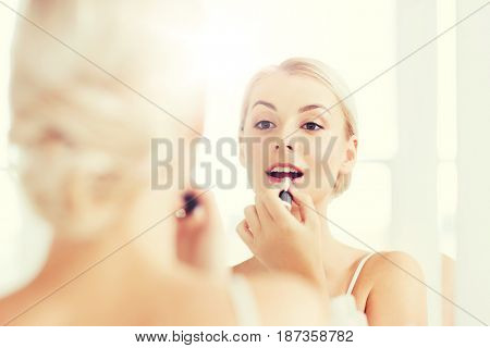 beauty, make up, cosmetics, morning and people concept - smiling young woman with lipstick applying makeup and looking to mirror at home bathroom