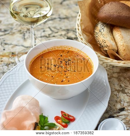 Peranakan cuisine. Singapore Laksa soup served with glass of white wine, bread, ceramic spoon, crab chips, slice of lemon and fresh vegetables on marble table