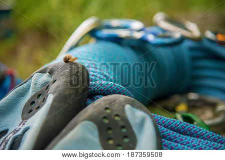 Close up Used equipment for climbing where the rope carbines and climbing slippers lie on a rock