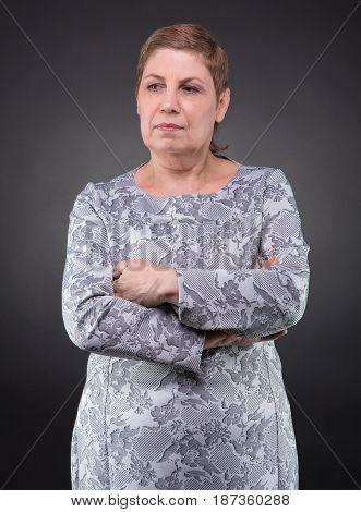 Portrait of thoughtful senior woman on dark background