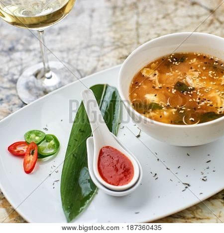 Korean cuisine. Spicy kimchi soup in white ceramic bowl served with red sauce in spoon, green leaf and paprika rings with glass of white wine on marble table.