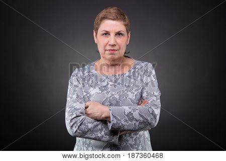 Portrait of old woman looking at camera on dark background