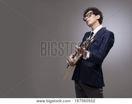 Funny man in striped suit with funny facial expression playing electric guitar