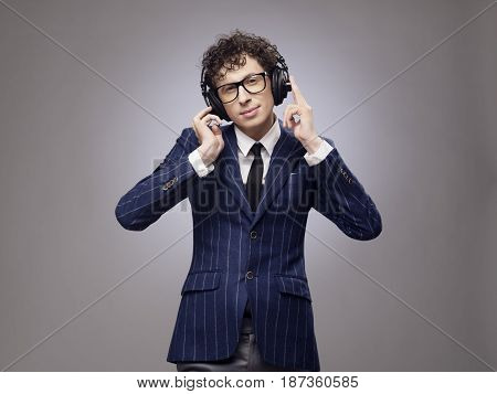 Funny man in headphones listening music studio shot on gray background